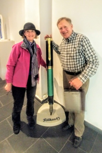 John and Nanci Taylor posting in front of a large Pelikan fountain pen